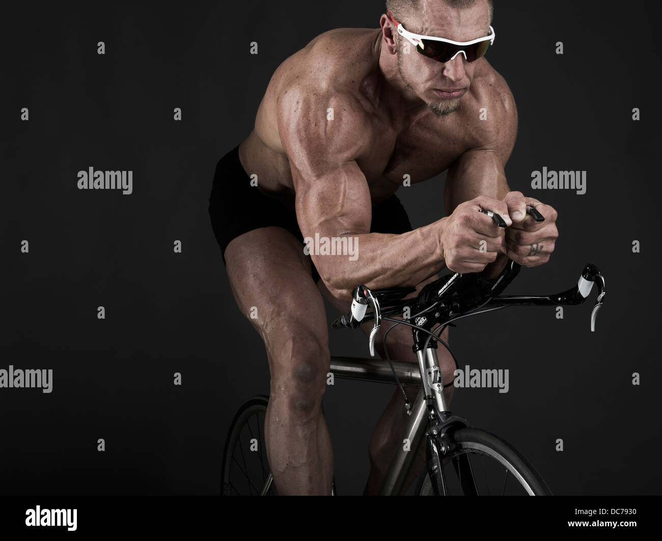 muscular triathlete on racing bicycle Stock Photo