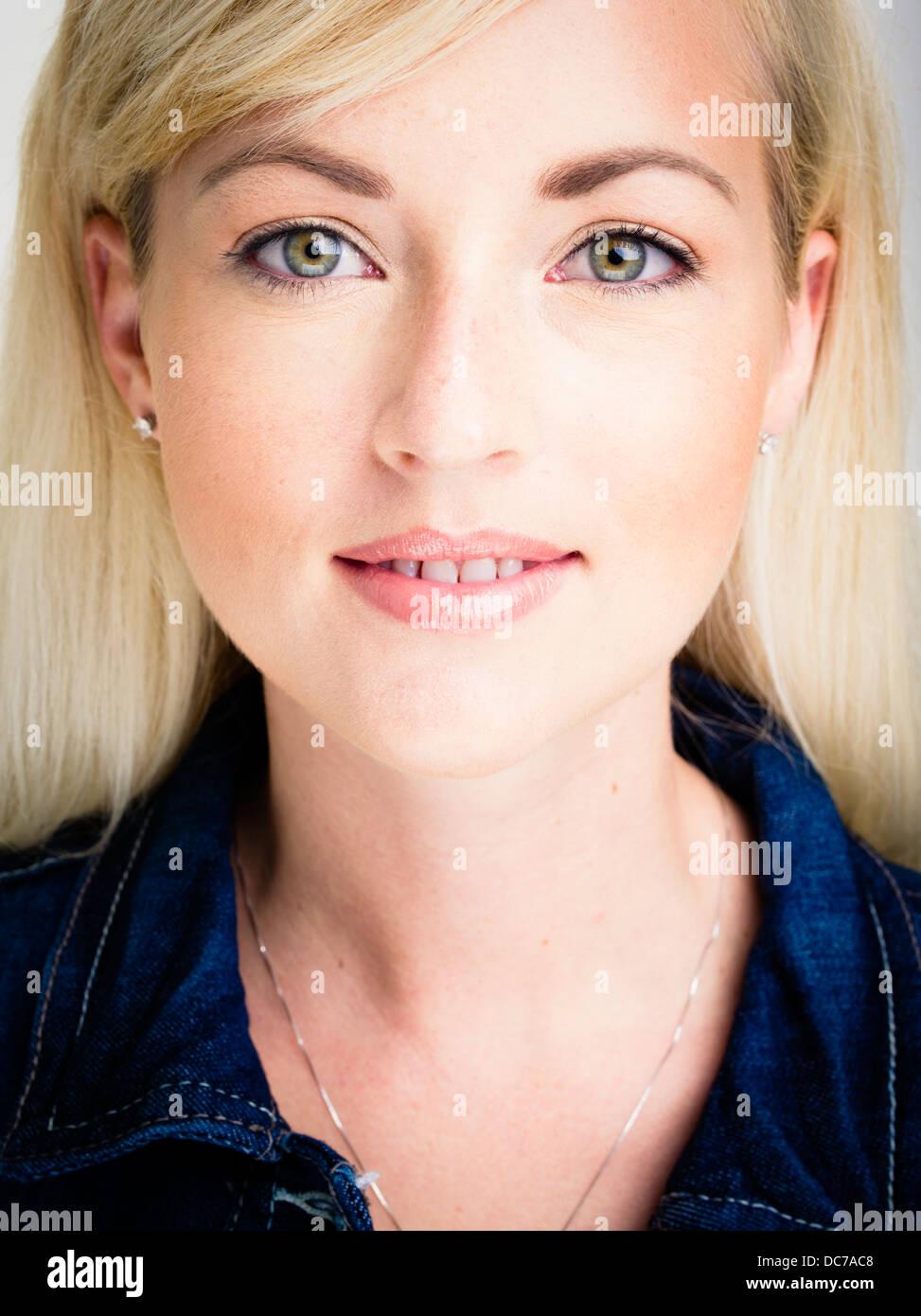 Beautiful blond Caucasian woman in her twenties wearing blue denim jacket - Stock Image