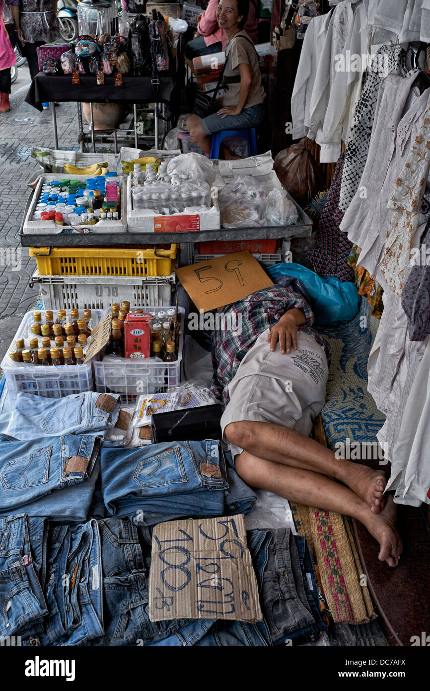 Pavement clothes vendor taking a mid- day nap. Man asleep at work. Thailand Asia - Stock Image