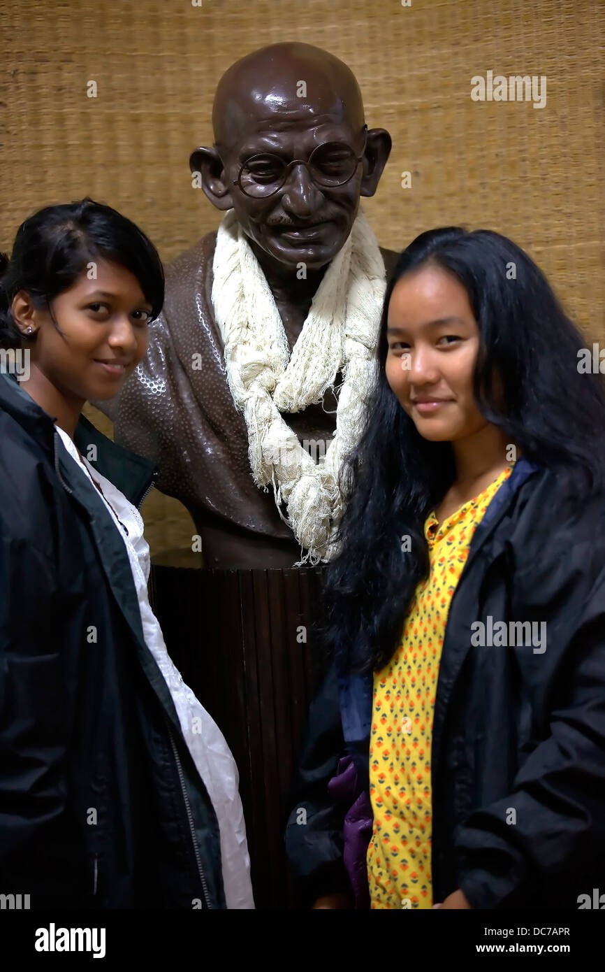 young,girls,female,two,teenager,standing,Mumbai together smiling happy cheerful friends Indian Mahatma Gandhi Statue - Stock Image