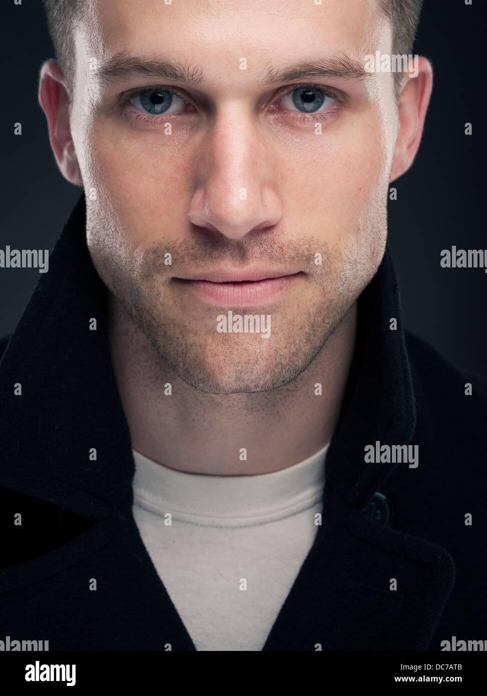 Handsome Caucasian man in white t-shirt and dark wool pea coat ( jacket ) - Stock Image