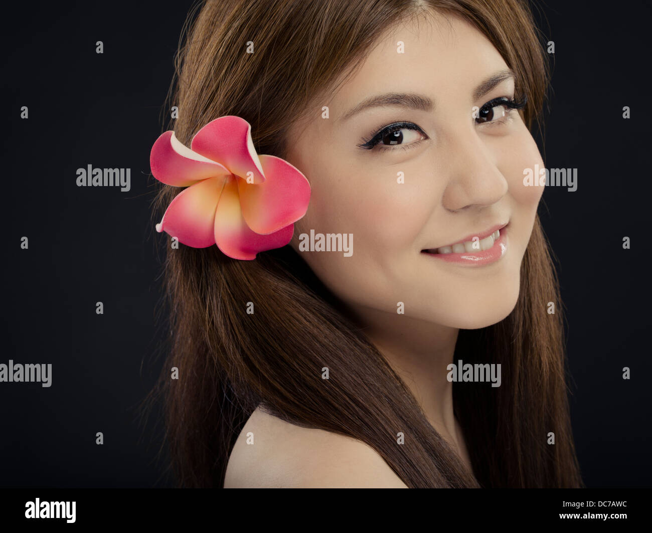 Plumeria stock photos plumeria stock images alamy beautiful young woman in her twenties smiling with plumeria flower in her hair over the right izmirmasajfo