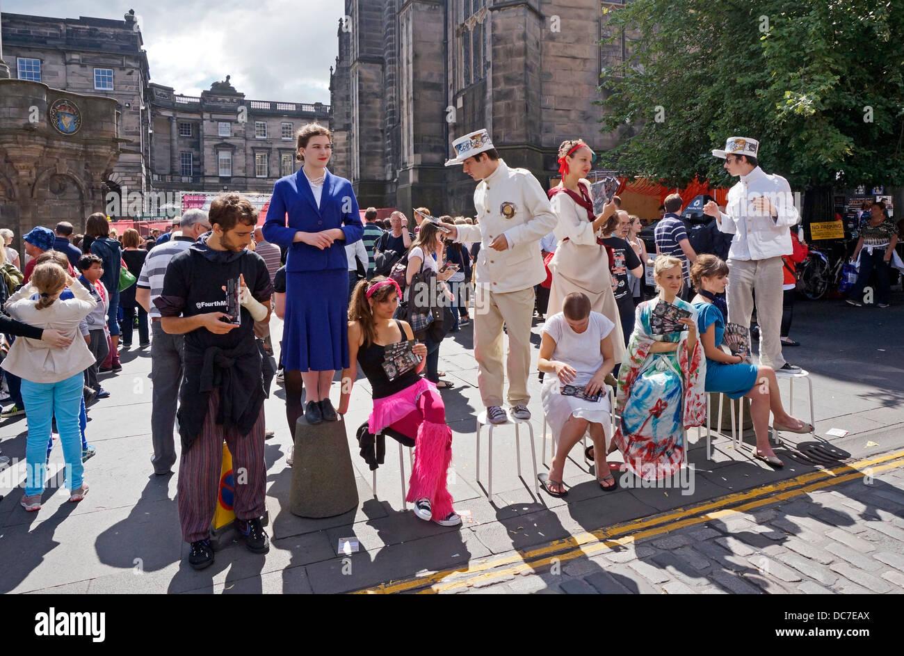 Fringe performers Fourth Monkey promoting shows in The Royal Mile Edinburgh during the 2013 Edinburgh Festival Fringe - Stock Image