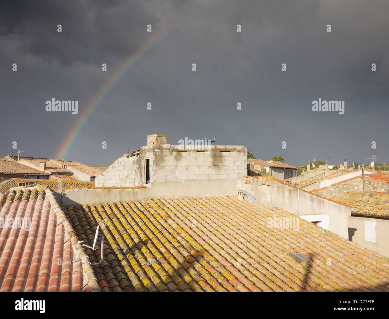 Rainbow over a roof tops Ginestas, France - Stock Image