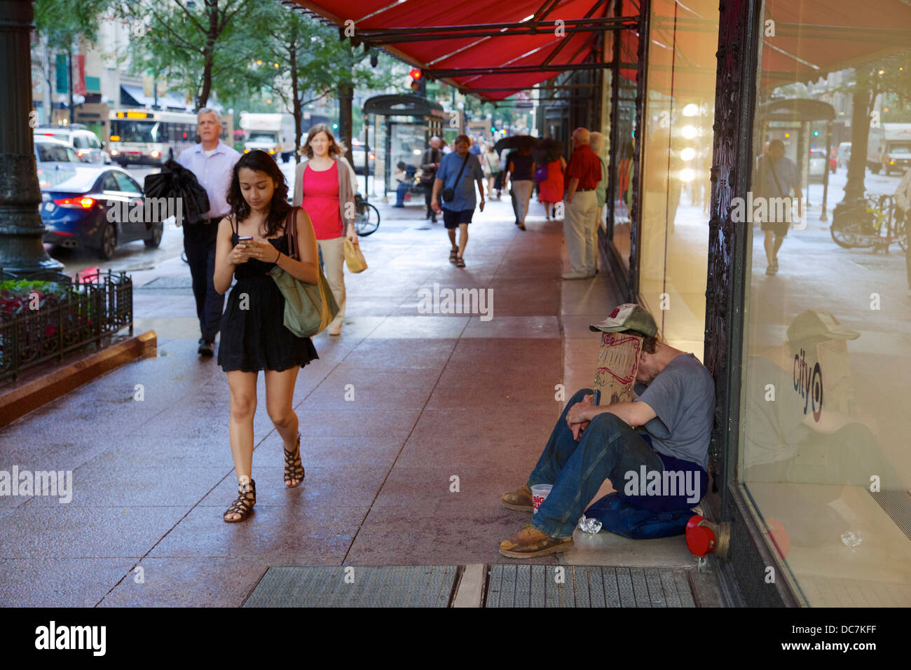 Homeless man, passerby texting. State Street, Chicago Illinois - Stock Image