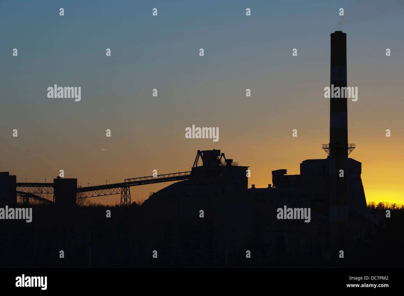 Silhouetted sunset view of industrial plant - Stock Image