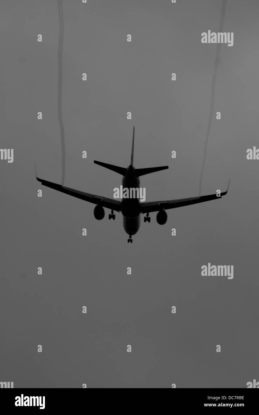 Aircraft on final approach showing wake trails - Stock Image