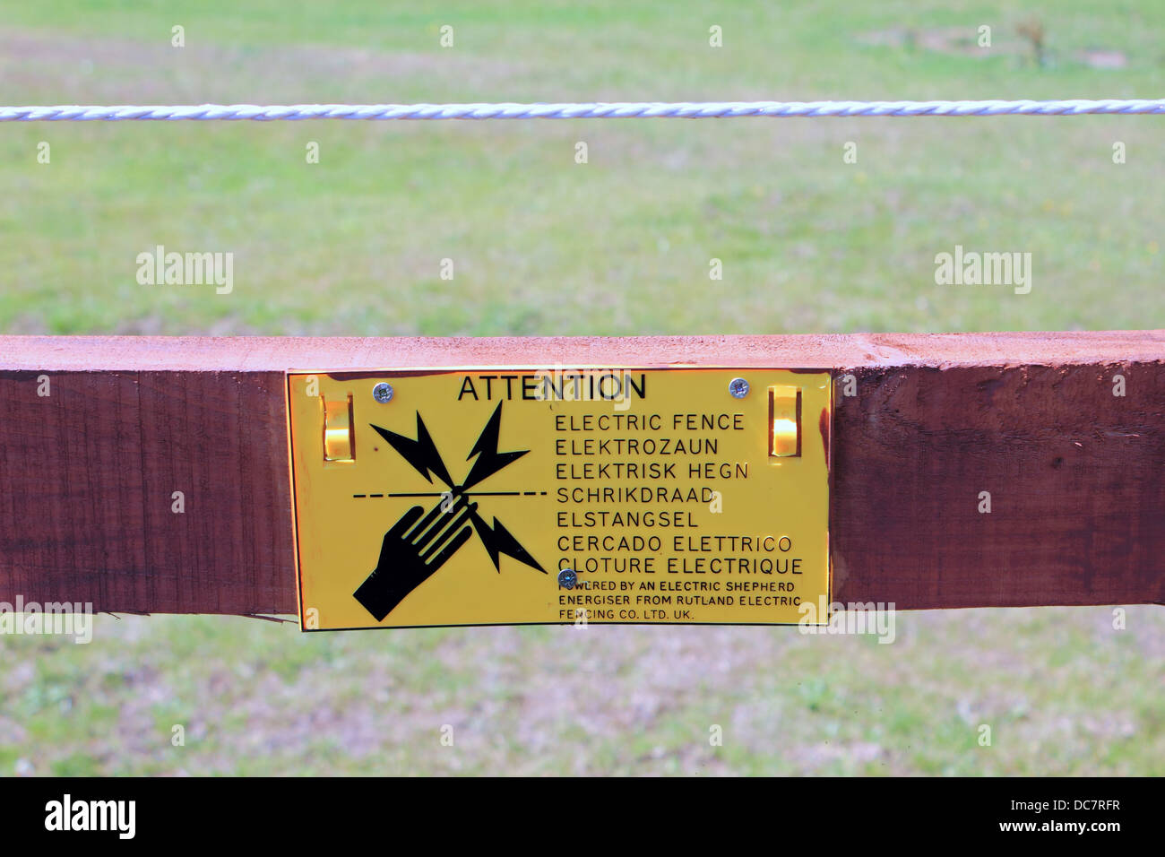 Attention electric fence sign in many languages. UK - Stock Image