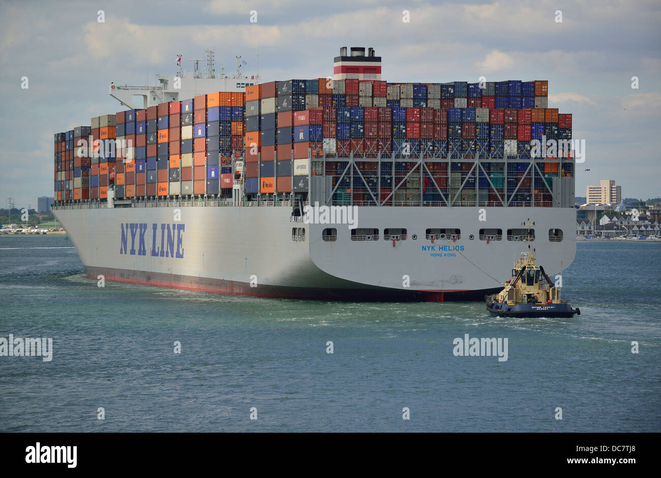Container ship  in Southampton Waters  with a rear brake tug assisting ship to its docking berth at Southampton - Stock Image