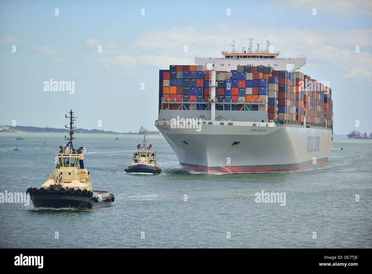 Container ship  in Southampton Waters  with two tugs assisting ship to its docking berth at Southampton , UK - Stock Image
