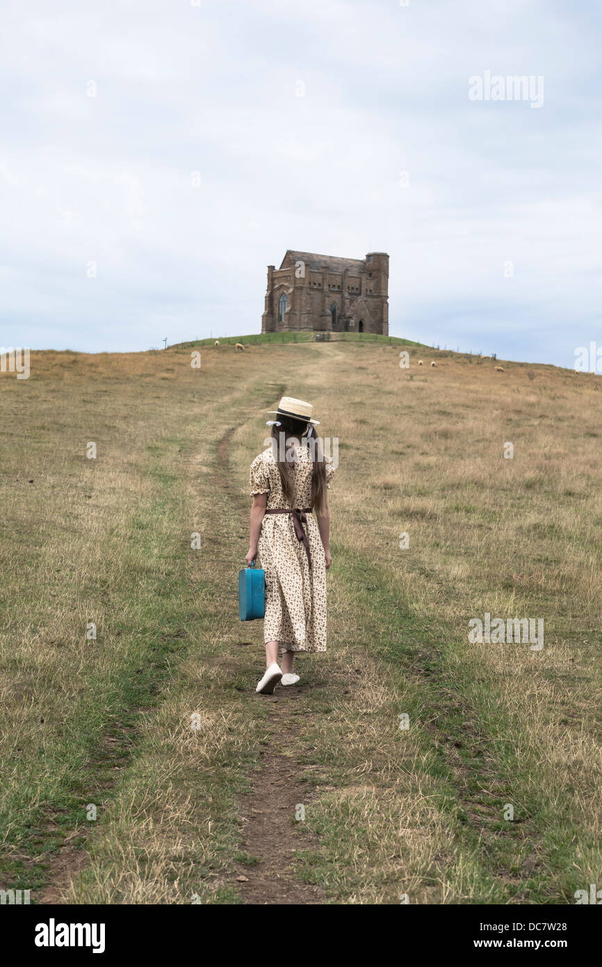 a girl in a vintage dress is walking uphill to a chapel - Stock Image