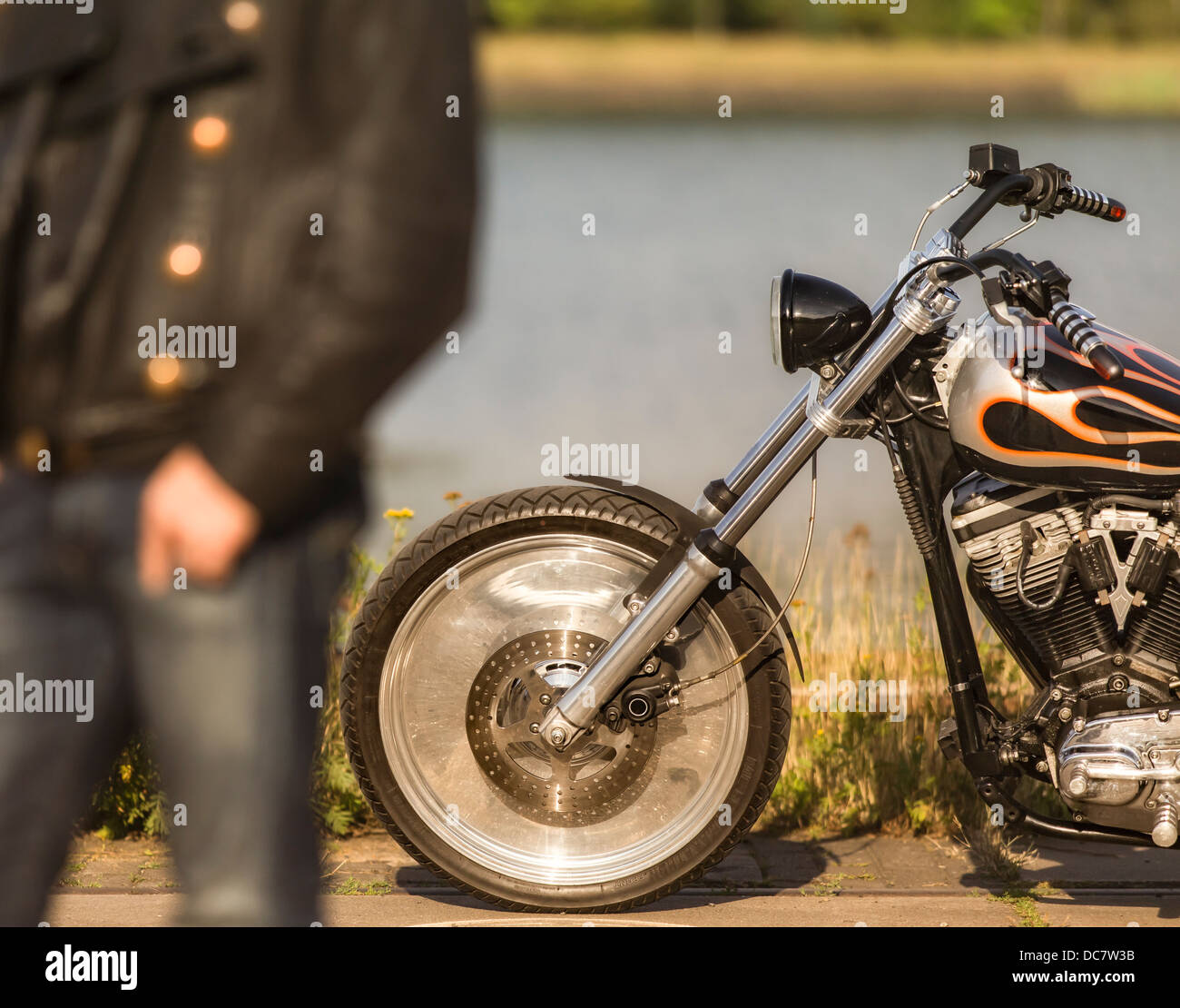 Young man wearing leather clothes with his Harley Davidson - Stock Image