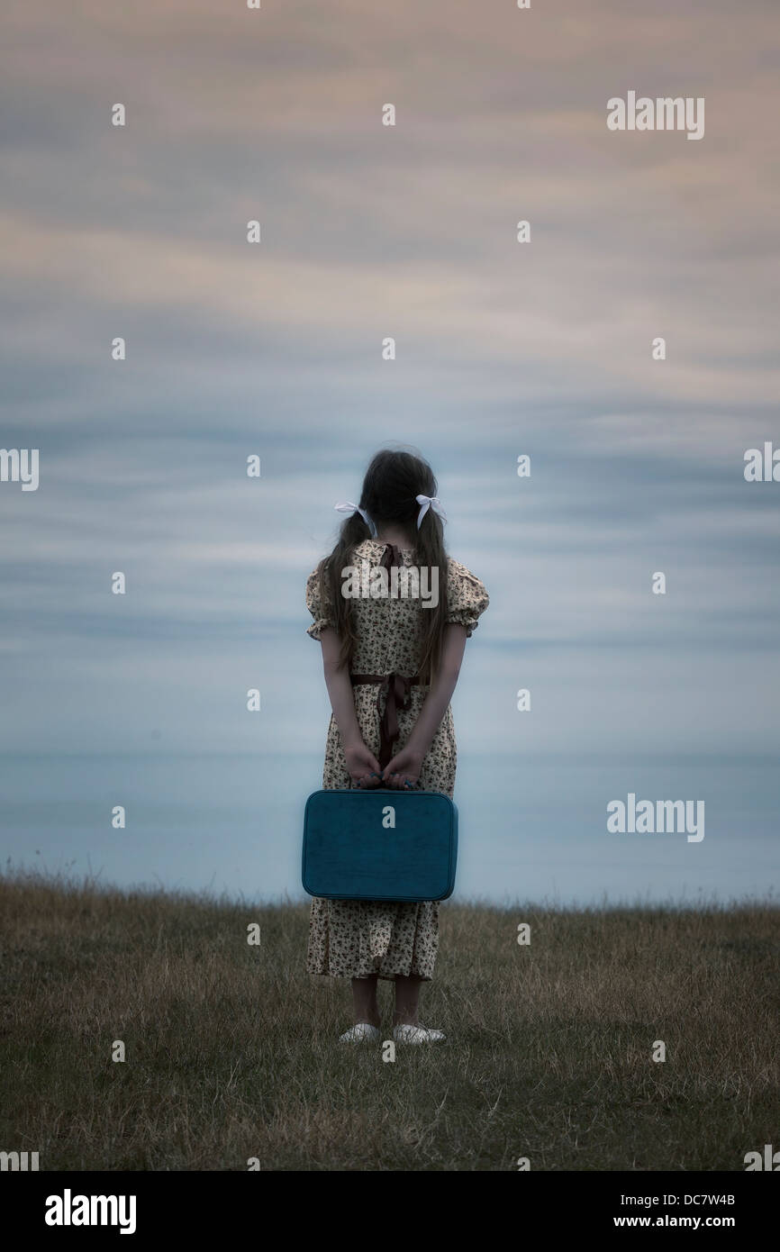 a girl in a vintage dress with suitcase - Stock Image