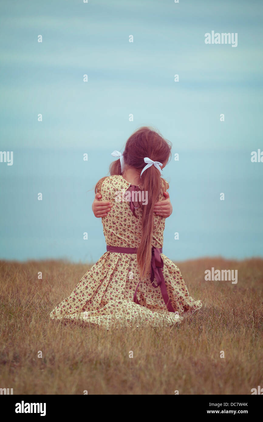 girl in a vintage dress, sitting on a meadow, hugging herself - Stock Image