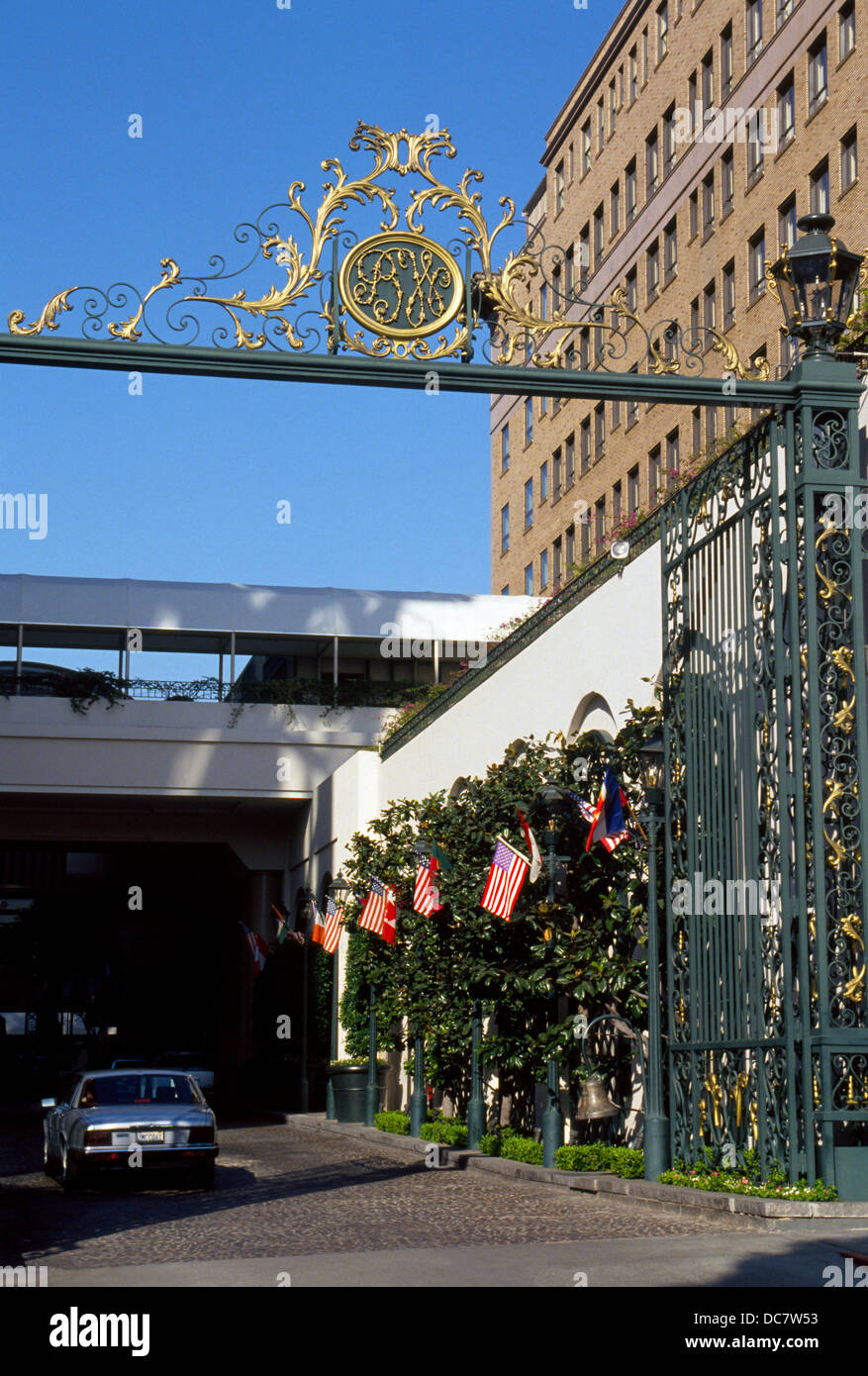 A gilded sign with the initials 'BW' marks the vehicle entry to the Beverly Wilshire hotel in Beverly Hills, - Stock Image