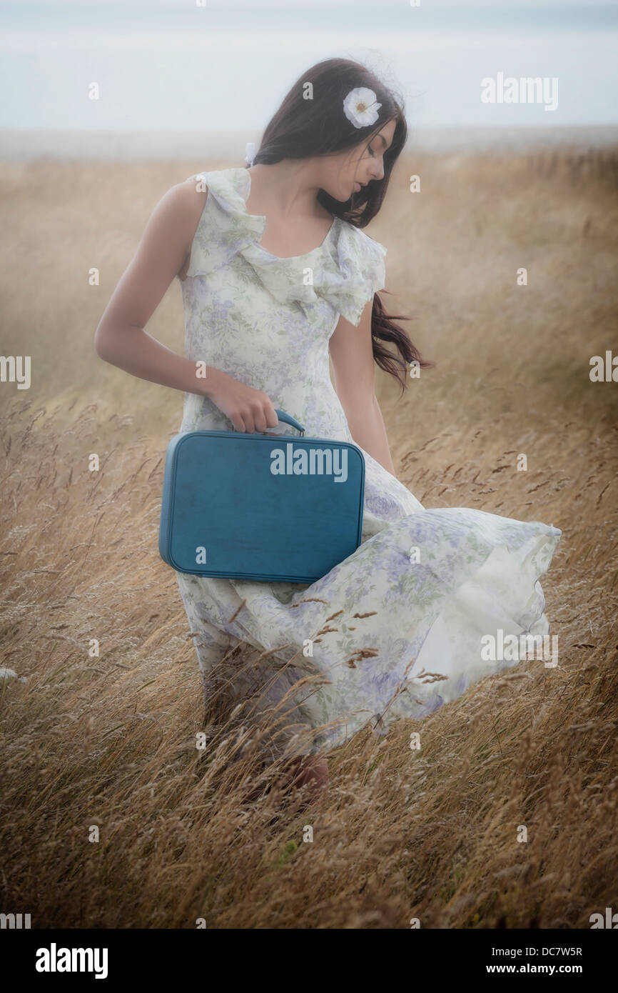a girl in a floral dress on a field with a suitcase - Stock Image