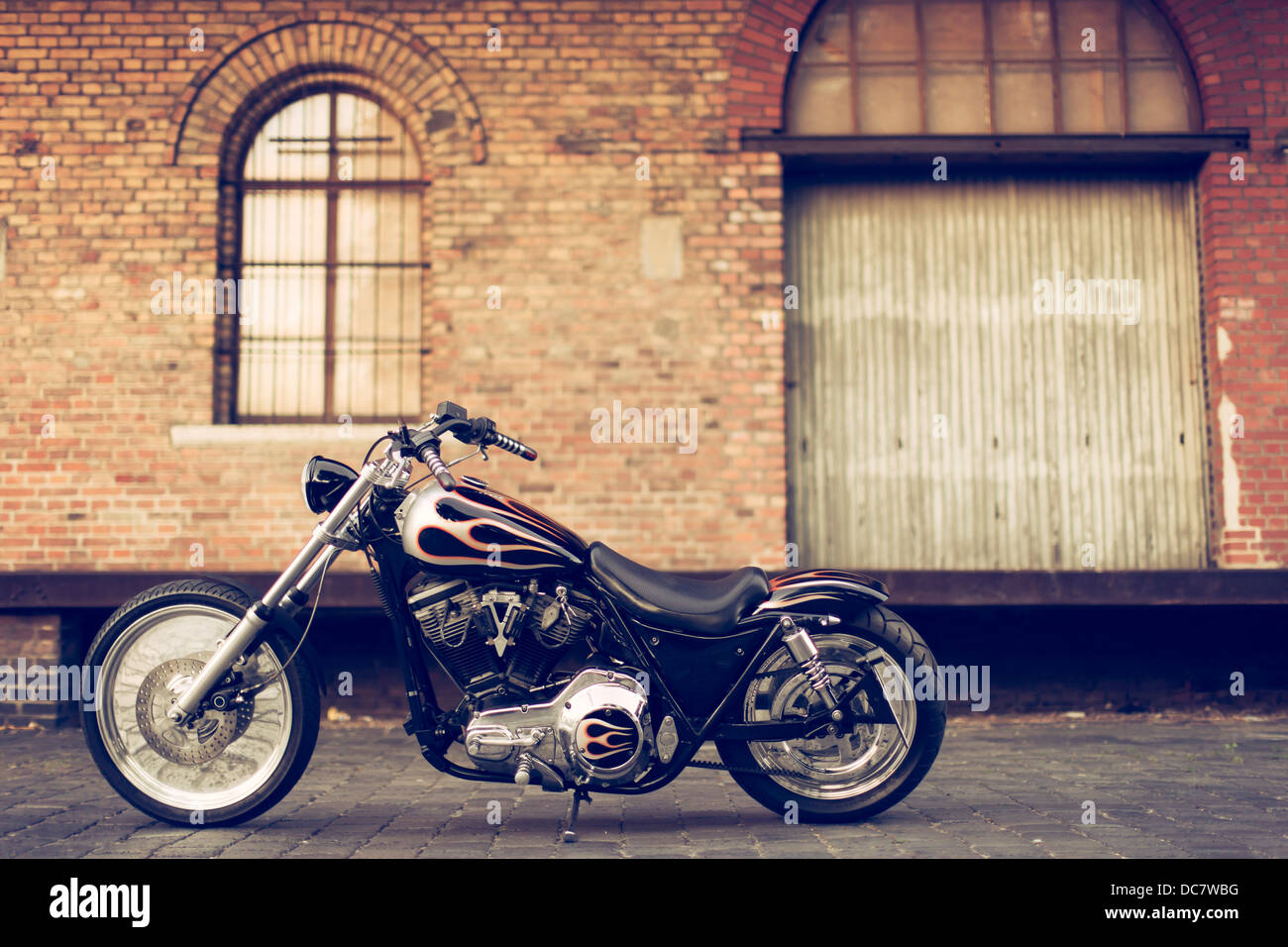 Harley Davidson in front of an old storage building - Stock Image
