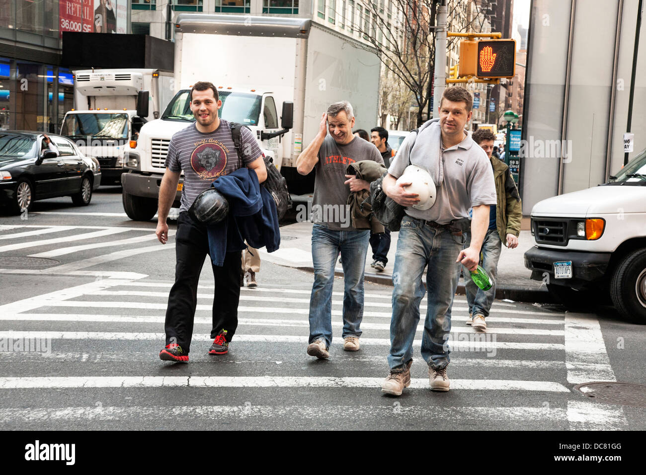 3 good natured construction workers in dusty work boots & carrying hard hats cross Broadway after work in midtown - Stock Image
