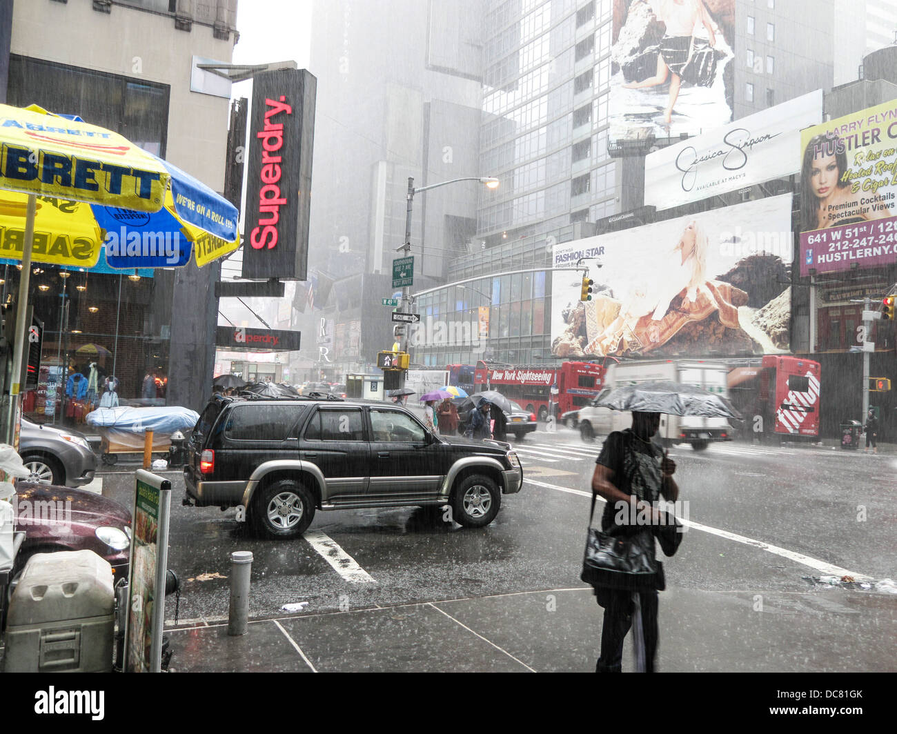 pedestrians brave awful weather as drenching summer rainstorm hits New York City & heavy rain veils advertising - Stock Image