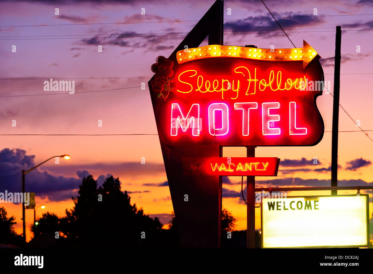 Bright neon sign for the Sleepy Hollows Motel with Vacancy and Welcome signs at dusk. Off the I-70 in Green River - Stock Image