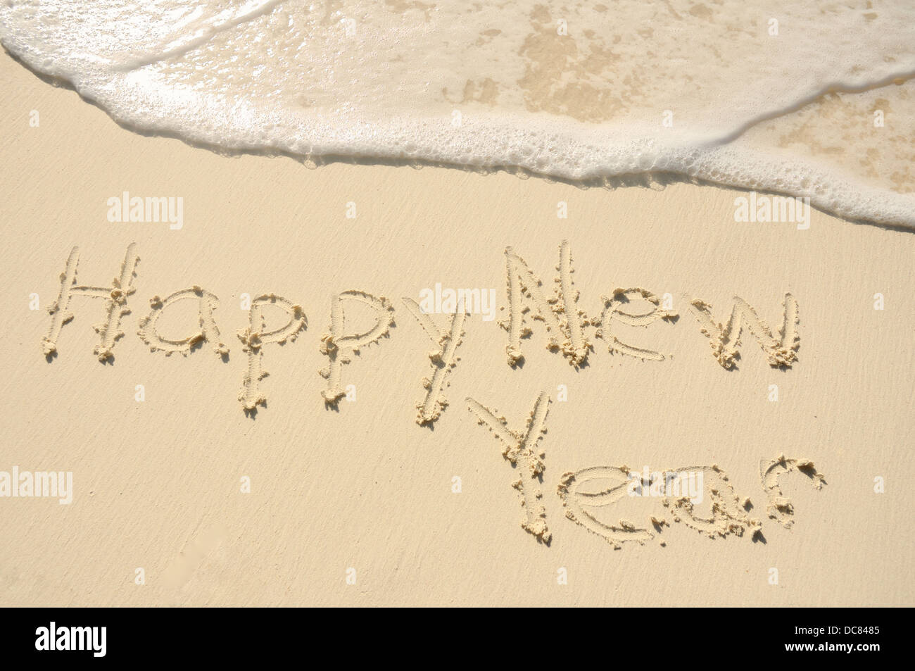 The Phrase 'Happy New Year' Written in the Sand on a Beach - Stock Image