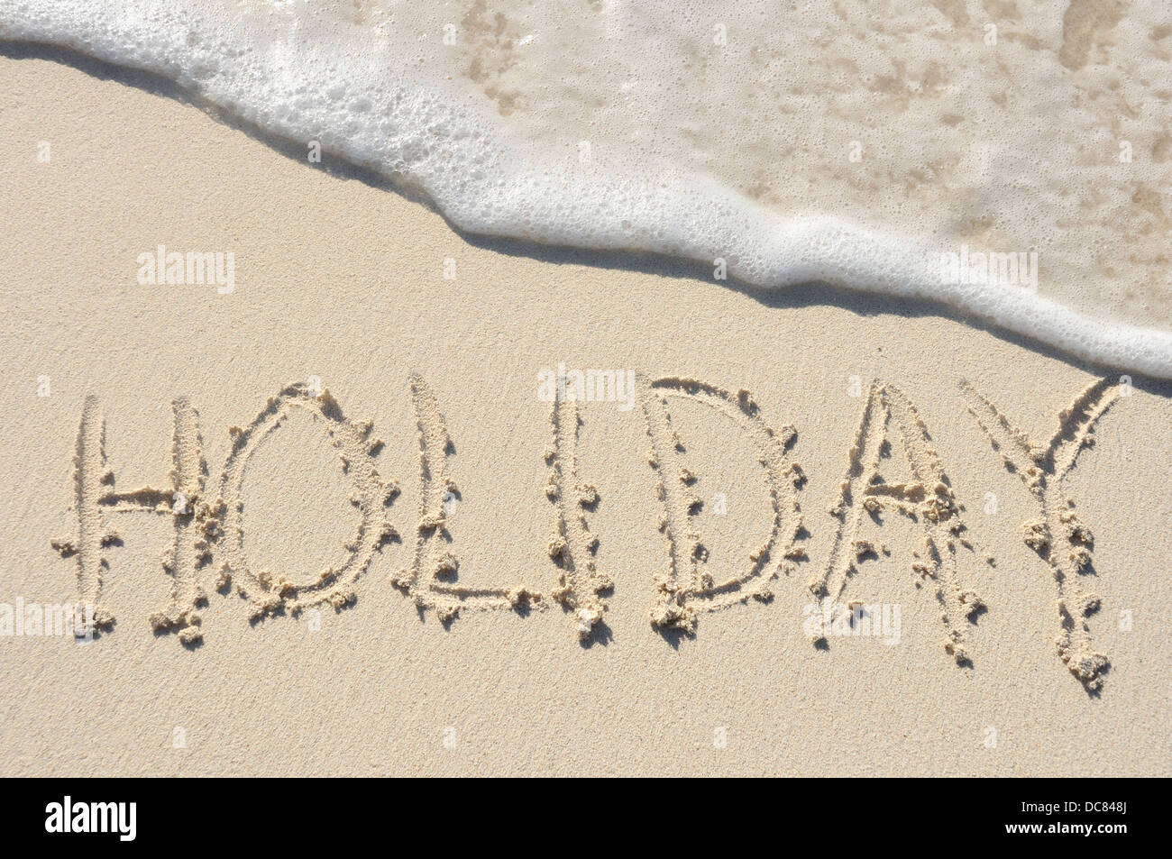 The Word 'Holiday' Written in the Sand on a Beach - Stock Image