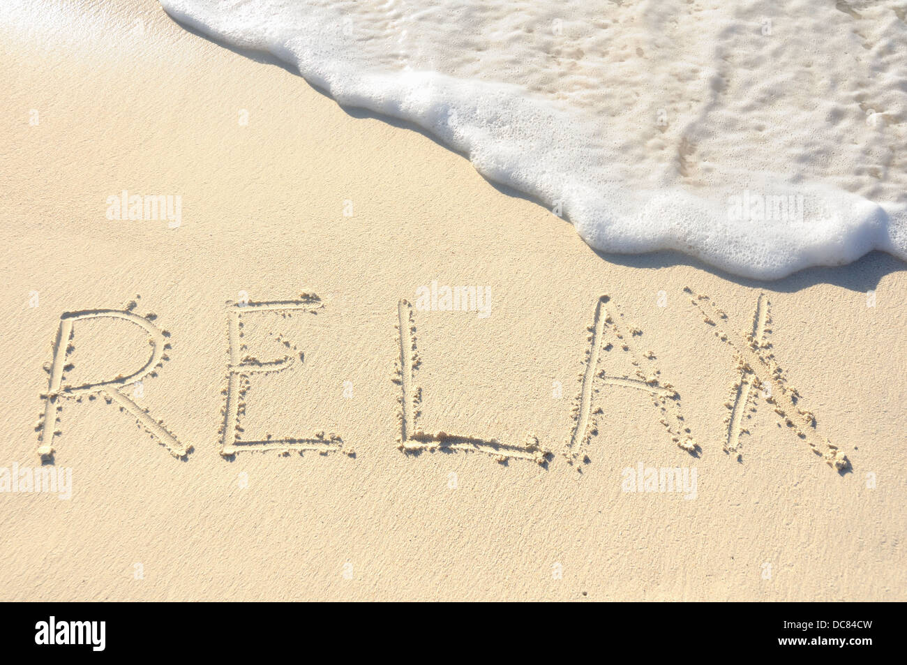 The Word 'Relax' Written in the Sand on a Beach - Stock Image
