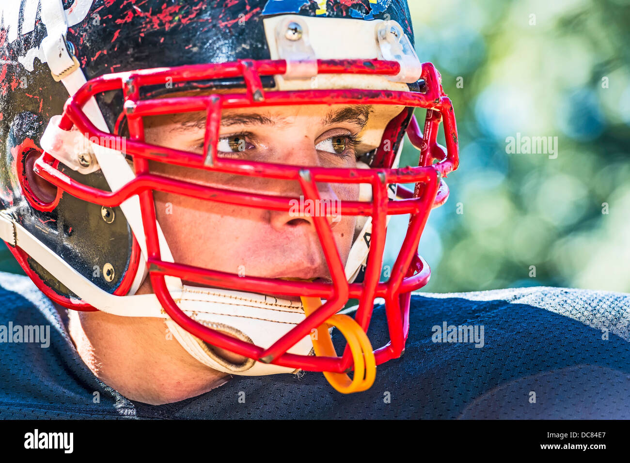 Portrait of a American Football Player with a heavily worn helmet - Stock Image