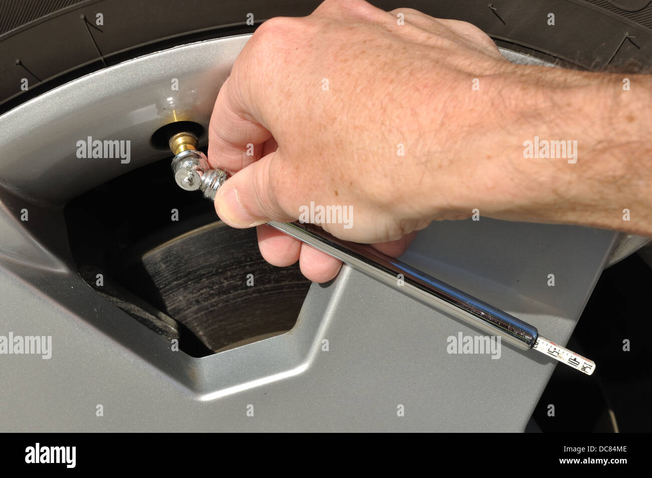 Checking tyre / tire pressure - Stock Image