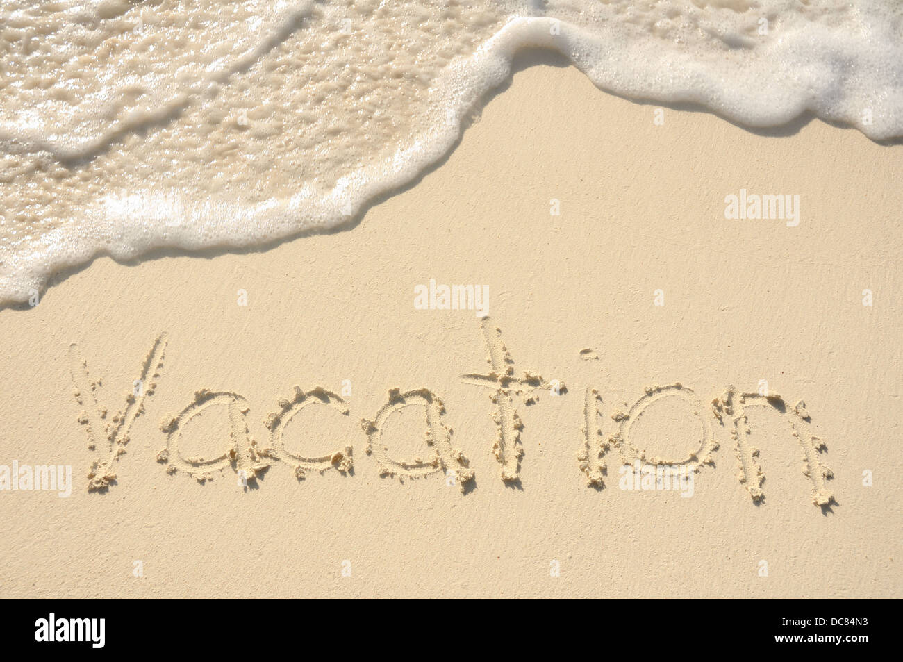The Word 'Vacation' Written in the Sand on a Beach - Stock Image