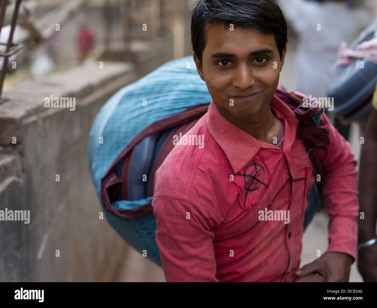 Young Indian man carrying goods in a shawl on the street in Varanasi India - Stock Image