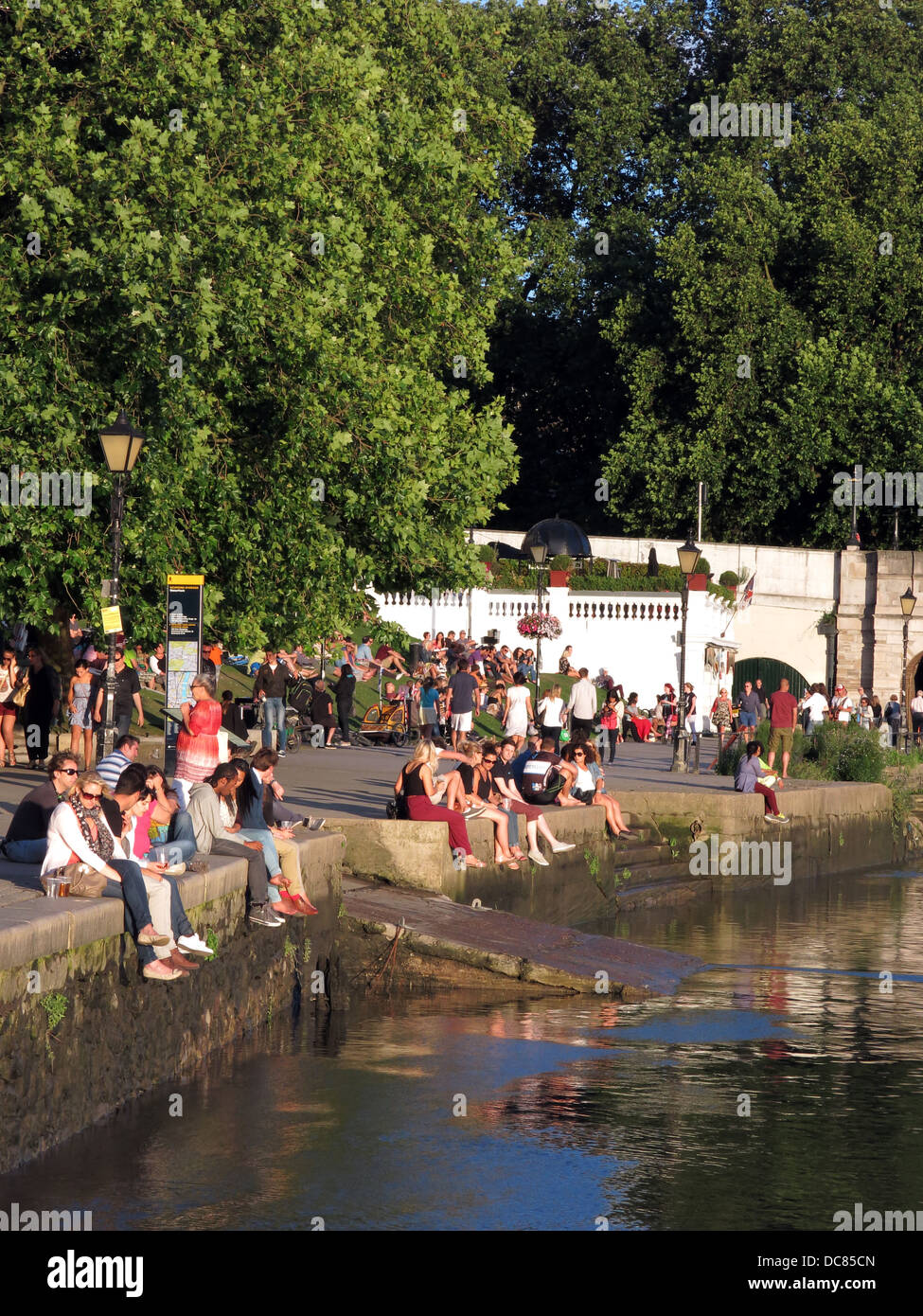 People relaxing on the Thames riverbank on a summer evening in Richmond. - Stock Image