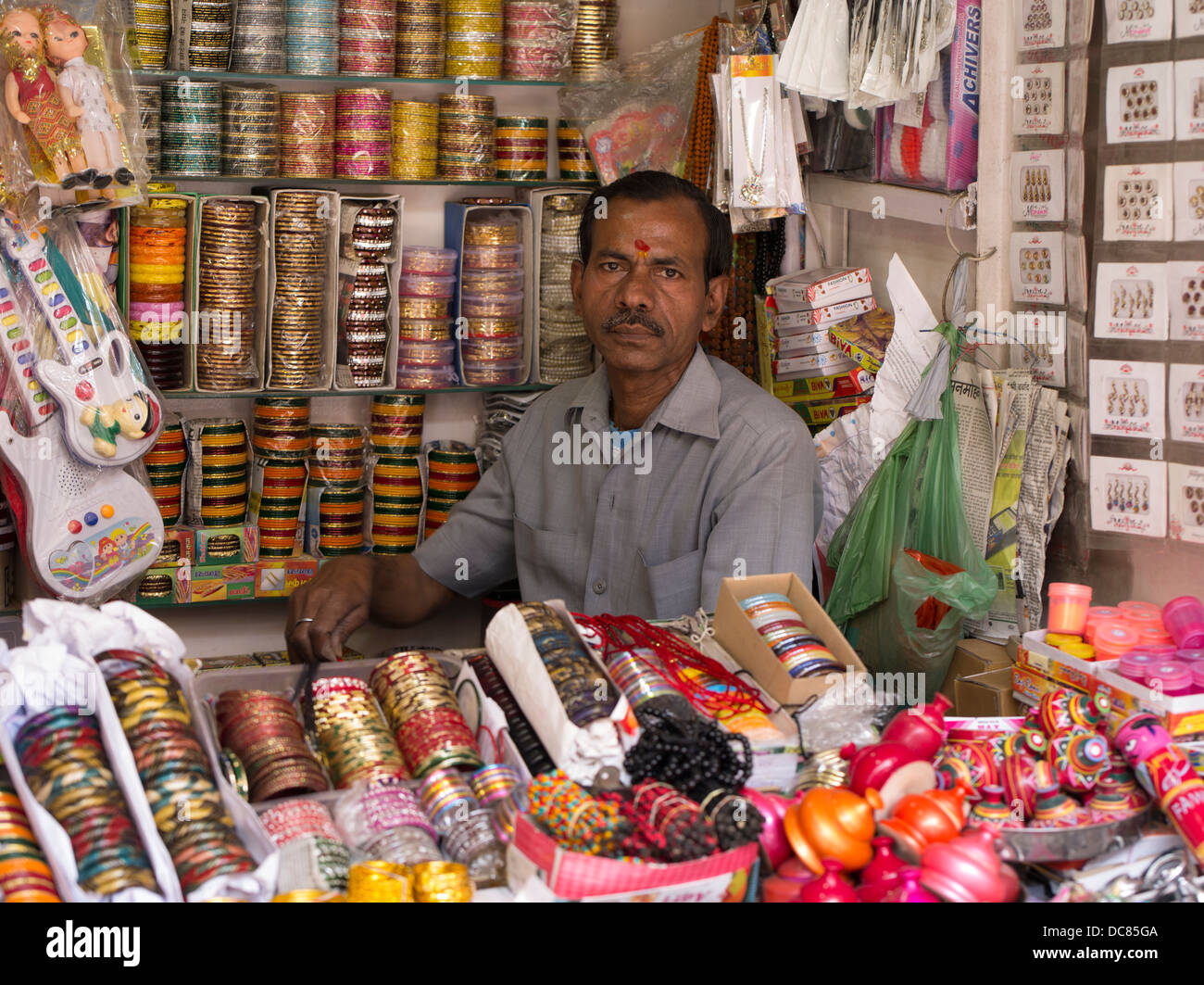 Shop owner with red tilak on forehead selling bangles in  Varanasi India - Stock Image