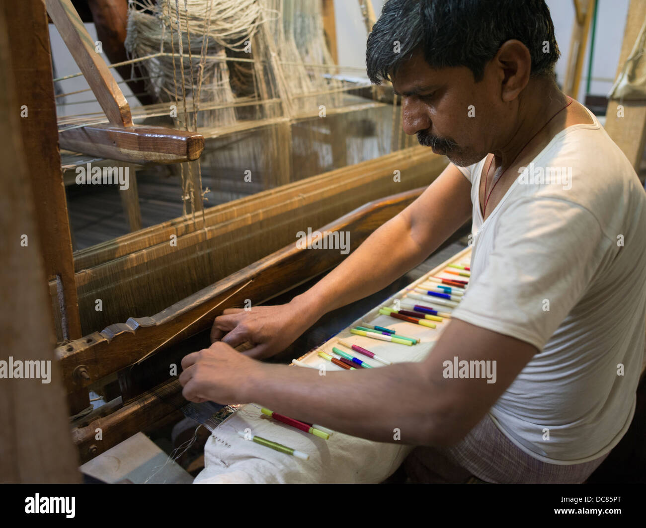 Weaver at a foot-treadle floor loom,  Varanasi, India - Stock Image