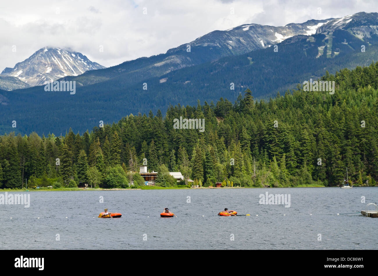 People having fun floating on on Alta Lake in Whistler, BC, Canada, in the summer. Mountains and forest in the background. - Stock Image