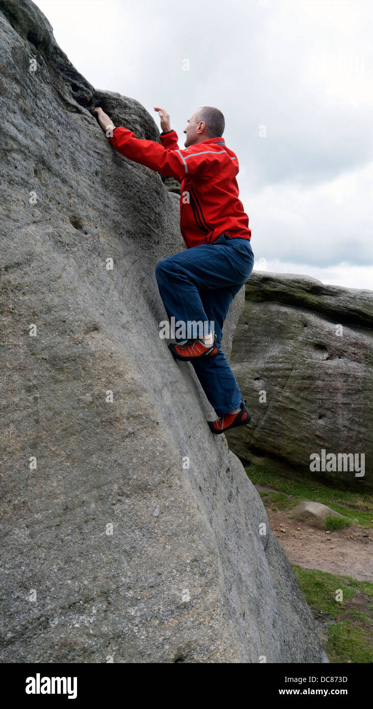 rock climber Doug Blane bouldering at Burbage Edge South, Derbyshire, Peak District National Park, England, UK, - Stock Image