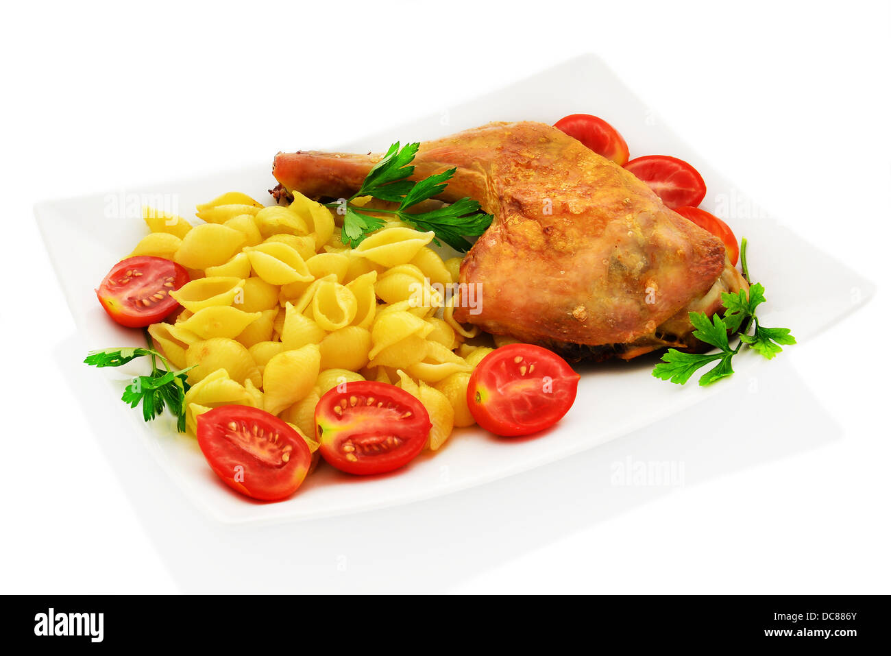 Chicken with pasta conchiglie, cherry tomatoes and parsley. Stock Photo