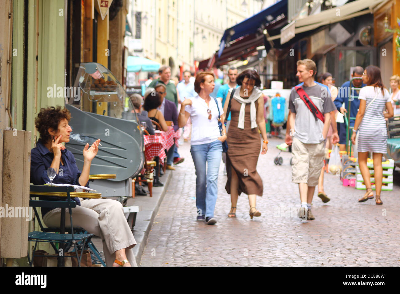 Mouffetard street in the 5th arrondissement of Paris - tourists strolling at paved street, lady smoking in the tiny - Stock Image