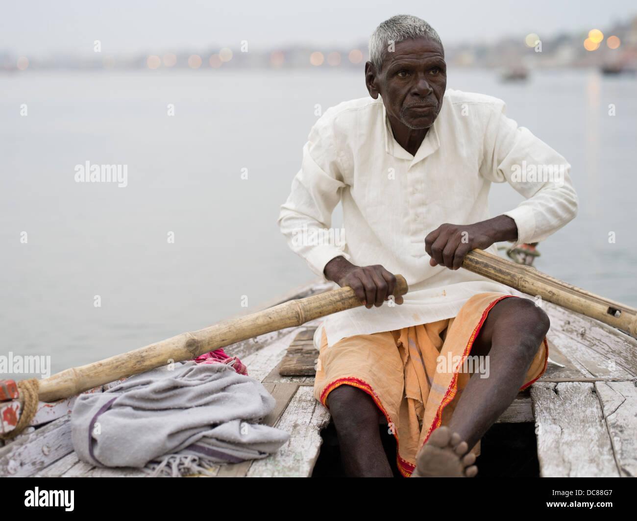 Boatman rowing on the Ganges River - Varanasi, India - Stock Image