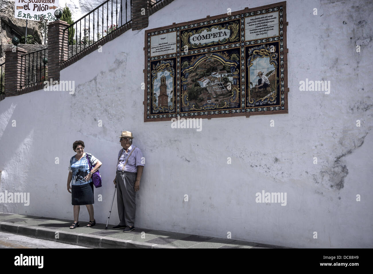Two residents of Competa chat under one of the tiled signs that are found in the whitewashed Andalusian town. - Stock Image