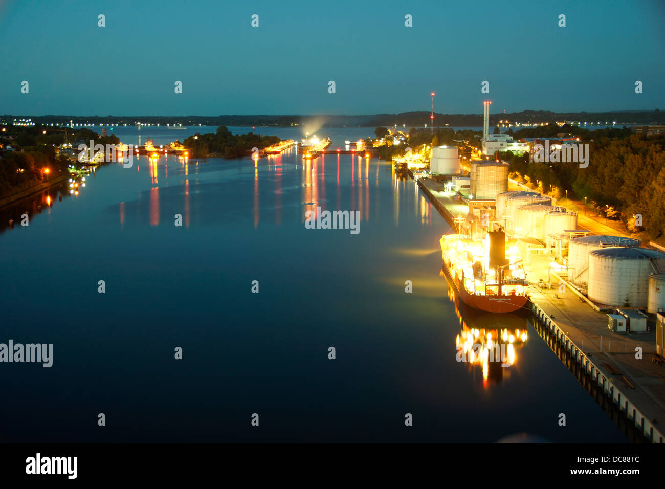 Long exposure of the canal lock KielHoltenau at night with a brightly lit ship Stock Photo