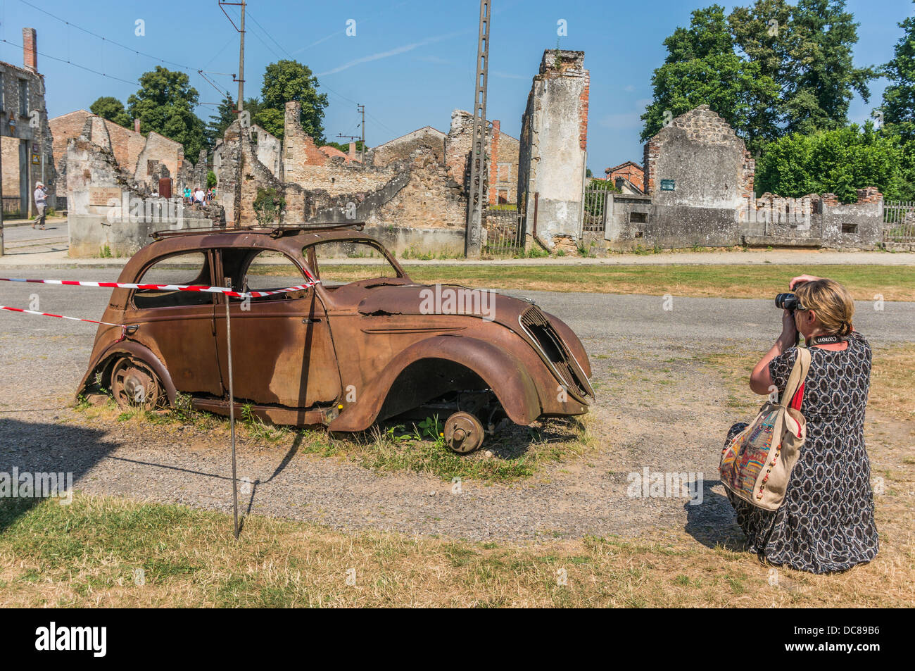 A woman taking a photograph of the iconic, left-to-rust 'Doctor's Car' among the ruins of Oradour-sur - Stock Image