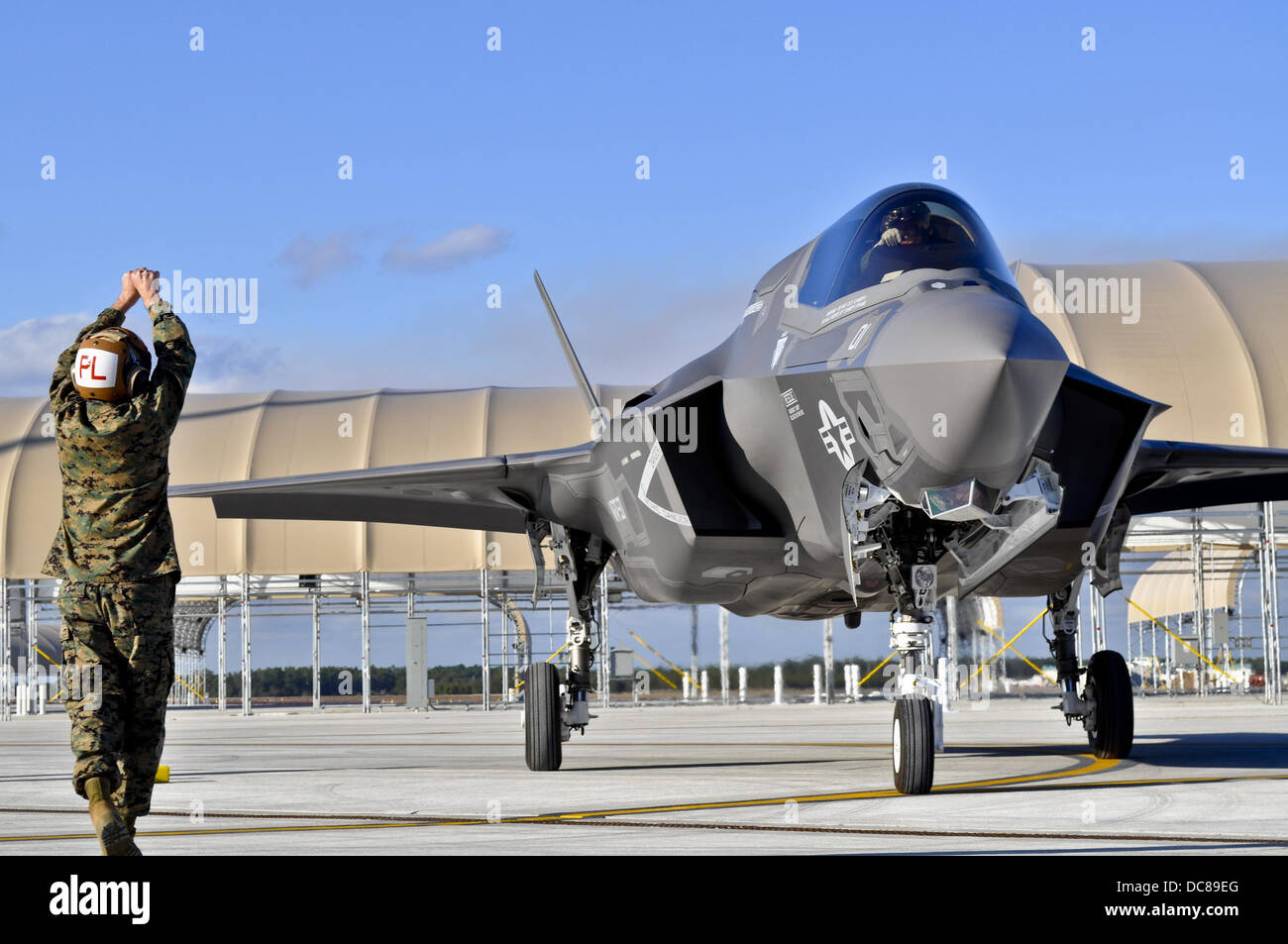 US Marine Gunnery Sgt. Matthew Smith marshals in the first Marine Corp F-35B Lightning II joint strike fighter to - Stock Image