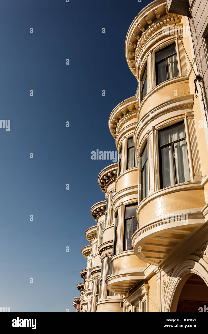Close-up view of pretty three story apartment houses with multiple bay windows lined up on neighborhood street in - Stock Image