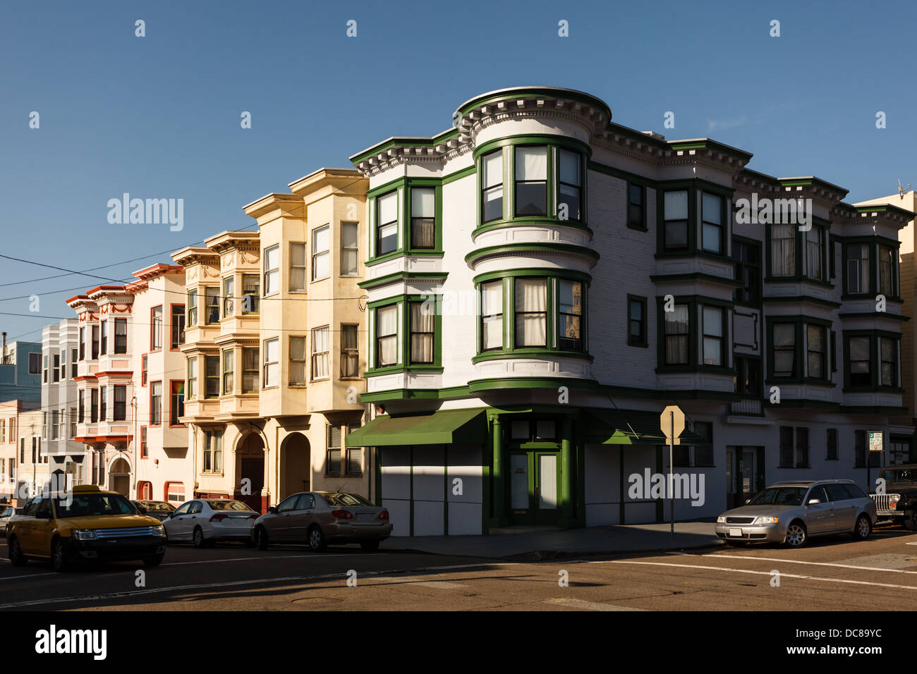 Corner of a pretty neighborhood street in San Francisco with three story apartment houses with bay windows - Stock Image