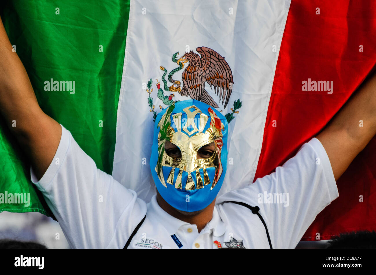 A man wears a Mexican wrestler's mask and holds up a Mexican flag - Stock Image