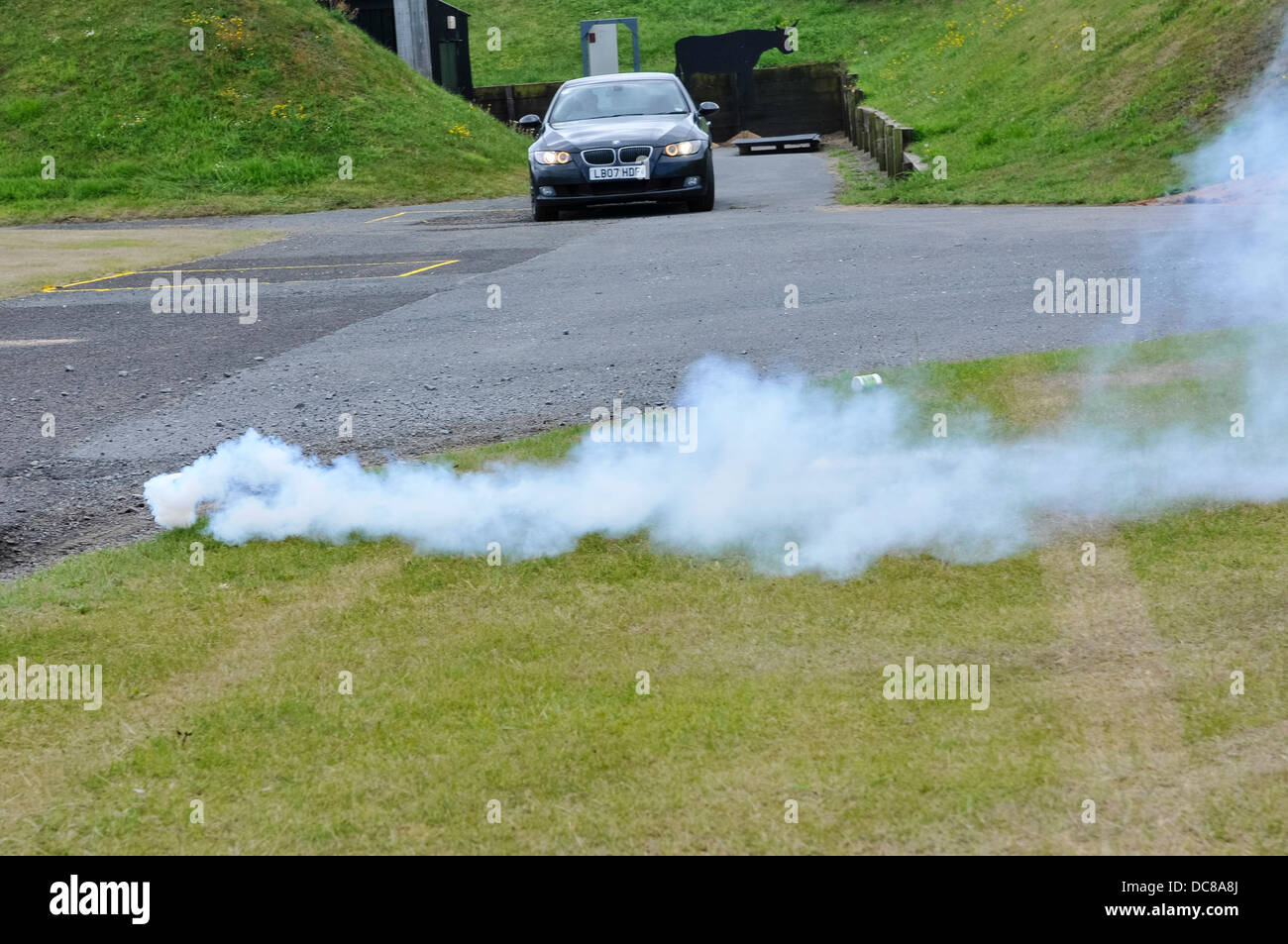 A smoke and blast grenade is thrown in front of a moving car to disorientate and distract the driver - Stock Image