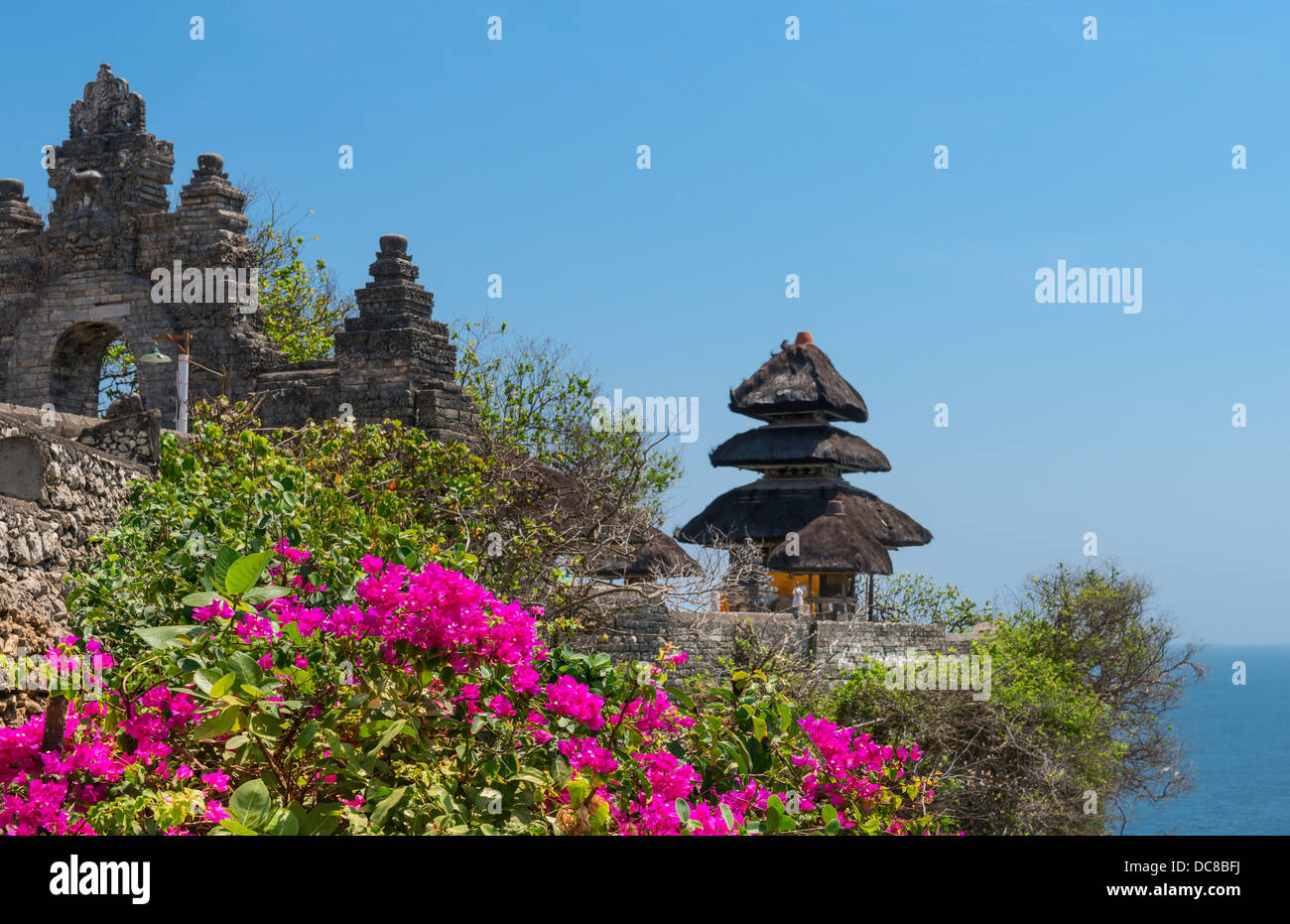 Pura Luhur Uluwatu Temple, Bali on cliffs above blue tropical sea with pink flowers on front - Stock Image