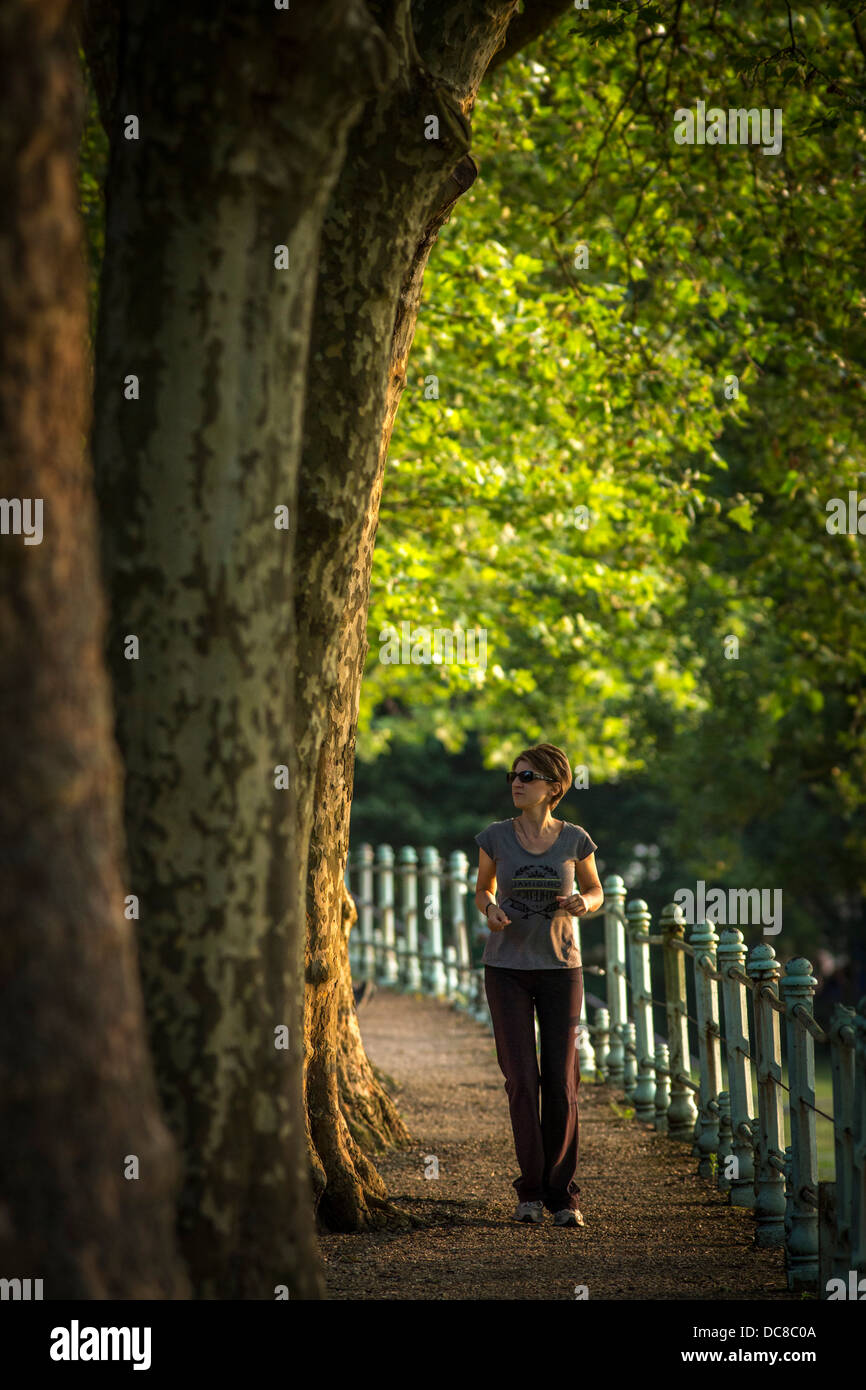 In Summer, a young woman jogging in a park of Vichy by a late afternoon (Allier - Auvergne - France). - Stock Image
