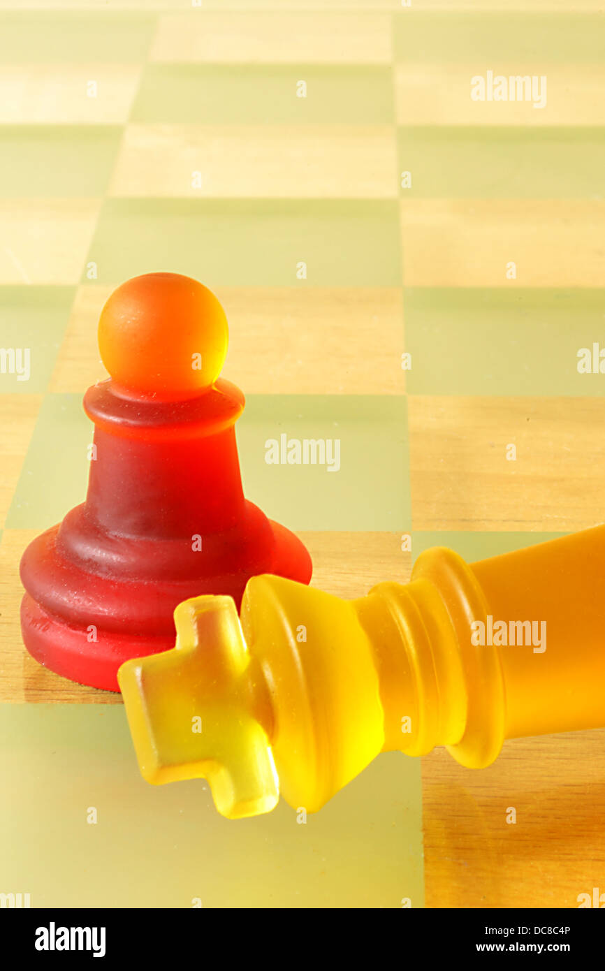 Never underestimate the power of a pawn. Chessboard with multi-colored players. - Stock Image